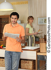 Young man reading a newspaper while his wife cooks dinner