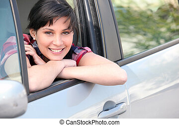 Woman leaning on the window of her car