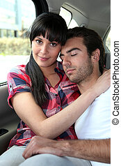 Tired couple in the back of a car