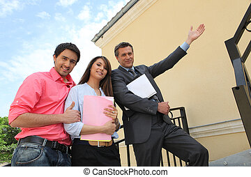 Couple with their realtor in front of their new house