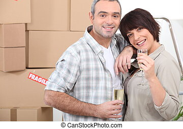 Moving day for a couple celebrating with champagne