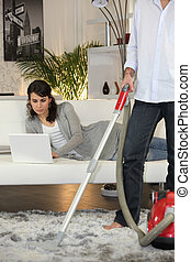 Man vacuuming and woman laid with laptop