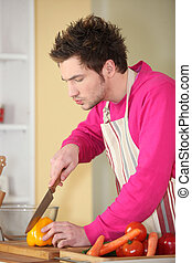 young man in kitchen cooking