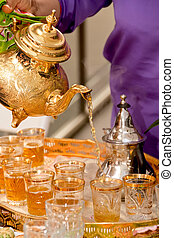 Arabic tea served in a golden teapot - Tray with cups of tea...