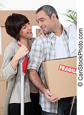 Couple moving into new home with boxes marked fragile