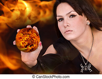 Witch in black dress with fire ball on flame - Aggressive...
