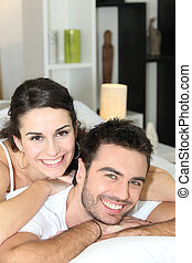 Young couple cheerful laid in bed
