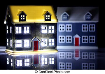 Two houses at night, one has lights