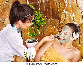 Young woman having clay body mask - Beautiful girl having...