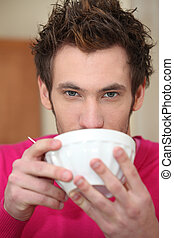 Young man drinking out of a bowl