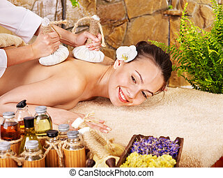 Woman getting thai herbal compress massage - Woman getting...