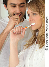 Couple brushing their teeth together