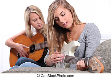 Two young women playing the guitar.