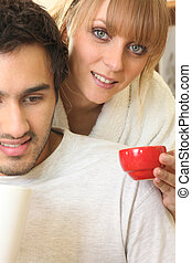 Young man sitting and young woman with cup of tea