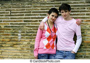 Boy and girl leaning against a wall
