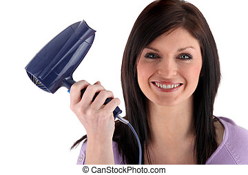 Happy woman holding hairdryer