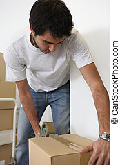 Young man taping shut a cardboard box