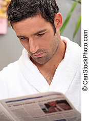 Handsome man in a toweling robe reading a journal