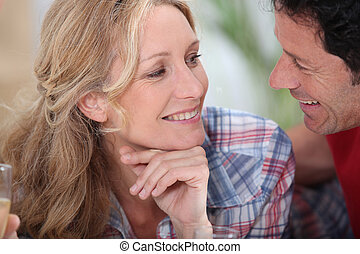 Smiling couple gazing intimately at each other with...