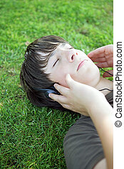 Portrait of a boy listening to music with headphones laid on...