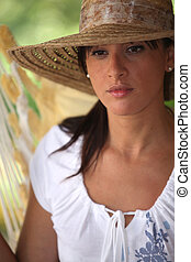 Contemplative woman in a straw hat sitting in a hammock