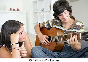 Young teenage couple with a guitar