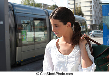 Young woman waiting at tram stop