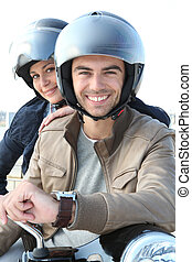 Man and woman smiling on a motorcycle