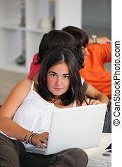 Teenage girl using a laptop at home with friends