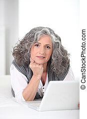Portrait of a Senior woman in front of a laptop computer