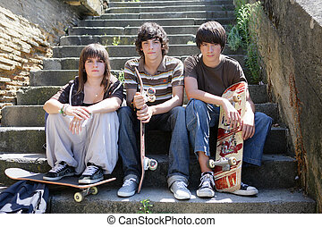 Three teen skateboarders sat on steps