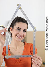 Woman holding house shaped measuring device