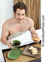 young man having breakfast in bed