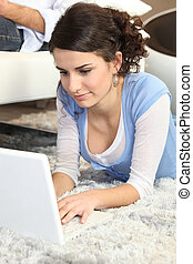 Young woman using a laptop on the floor at home