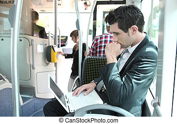 Man using laptop computer on a tram