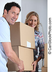 Couple moving a pile of large cardboard boxes
