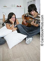 teenage brunette lost in admiration for boyfriend playing...