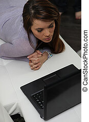 young woman lying and laptop