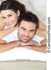 Young couple laying in bed