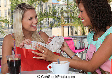 Two girls stopping for coffee on a shopping trip