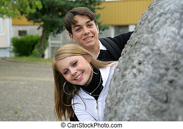 Adolescents peering out from behind a rock