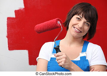 Woman painting wall red with roller