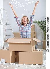 Woman joyously unpacking boxes
