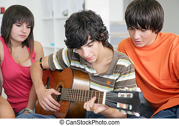 Teens listening to their peer play the guitar