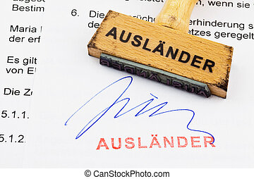 a stamp made of wood lying on a document. german inscription: foreigners