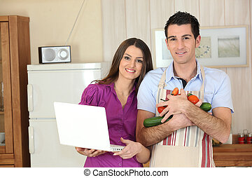 Couple in a kitchen with a laptop computer and arms full of vegetables