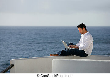 Man with computer in front of the sea