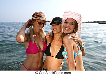 Three girlfriends posing in the sea on holiday