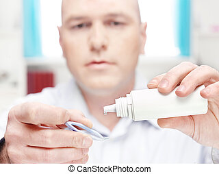 man clean contact lens at home, focus on drop of liquid from...