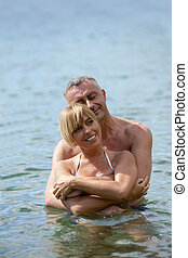 Middle-aged couple swimming